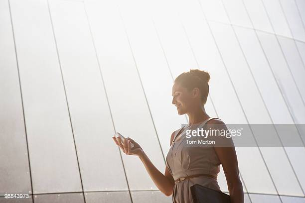Businesswoman text messaging on cell phone outdoors