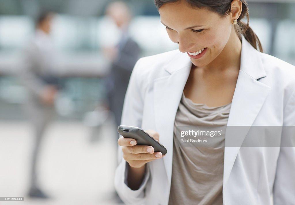 ビジネスウーマンのテキストメッセージを携帯電話 : ストックフォト