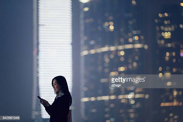 Businesswoman text messaging on smartphone in city