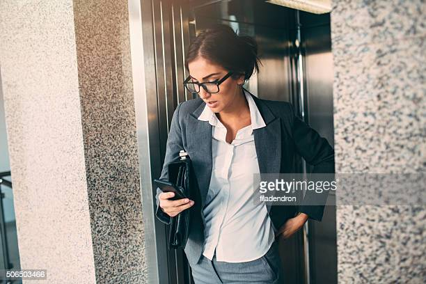 Businesswoman Texting  In The Elevator