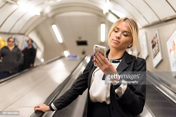businesswoman texting on escalator, london underground, uk - vertical red tube fotografías e imágenes de stock