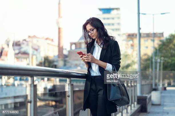 Businesswoman texting on her mobile phone