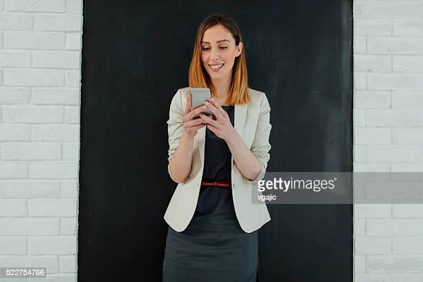 Businesswoman Texting On The Phone In Her Office.