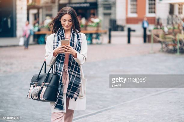 Businesswoman texting on the street