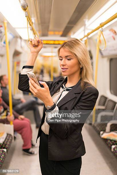businesswoman texting on tube, london underground, uk - vertical red tube fotografías e imágenes de stock