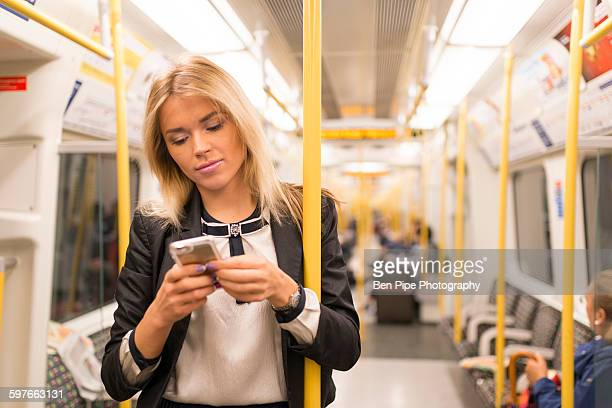 Businesswoman texting on tube, London Underground, UK