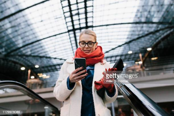 businesswoman texting on way to the office - bahnhof stock-fotos und bilder