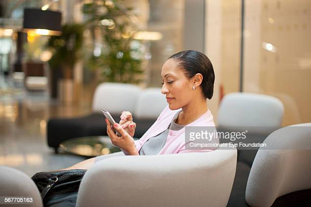 Businesswoman texting with cell phone in lobby