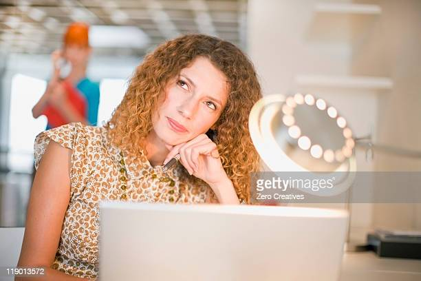Businesswoman thinking and using laptop