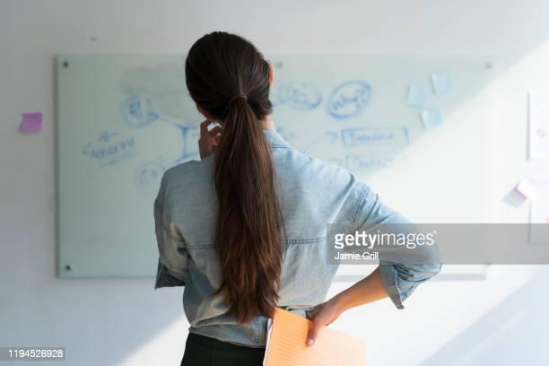 businesswoman thinking in front of whiteboard - paardenstaart haar naar achteren stockfoto's en -beelden