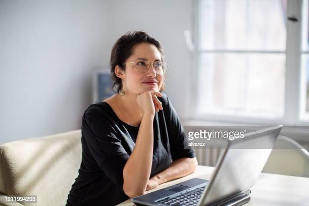 businesswoman thinking while working in office - contemplation stock pictures, royalty-free photos & images