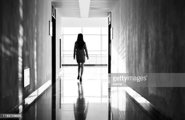 businesswoman through the office corridor - leaving stock pictures, royalty-free photos & images