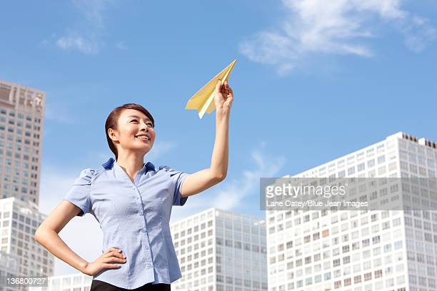 Businesswoman Throwing a Paper Airplane