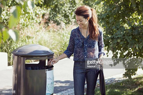 businesswoman throwing garbage in bin at park - garbage can stock photos and pictures