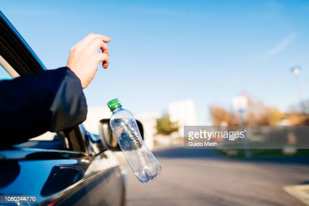 Businesswoman throwing garbage out of car window.