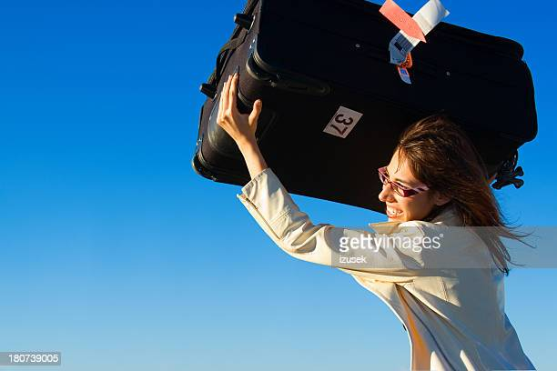 businesswoman throwing luggage bag - izusek stock pictures, royalty-free photos & images