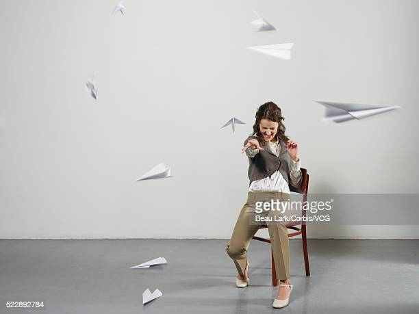 Businesswoman throwing paper airplanes