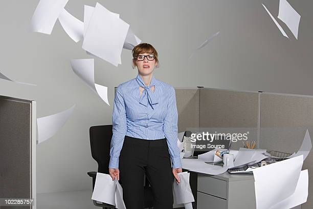 Businesswoman throwing paper into the air
