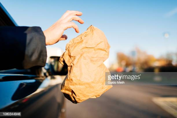 Businesswoman throwing trash bag out of car window.