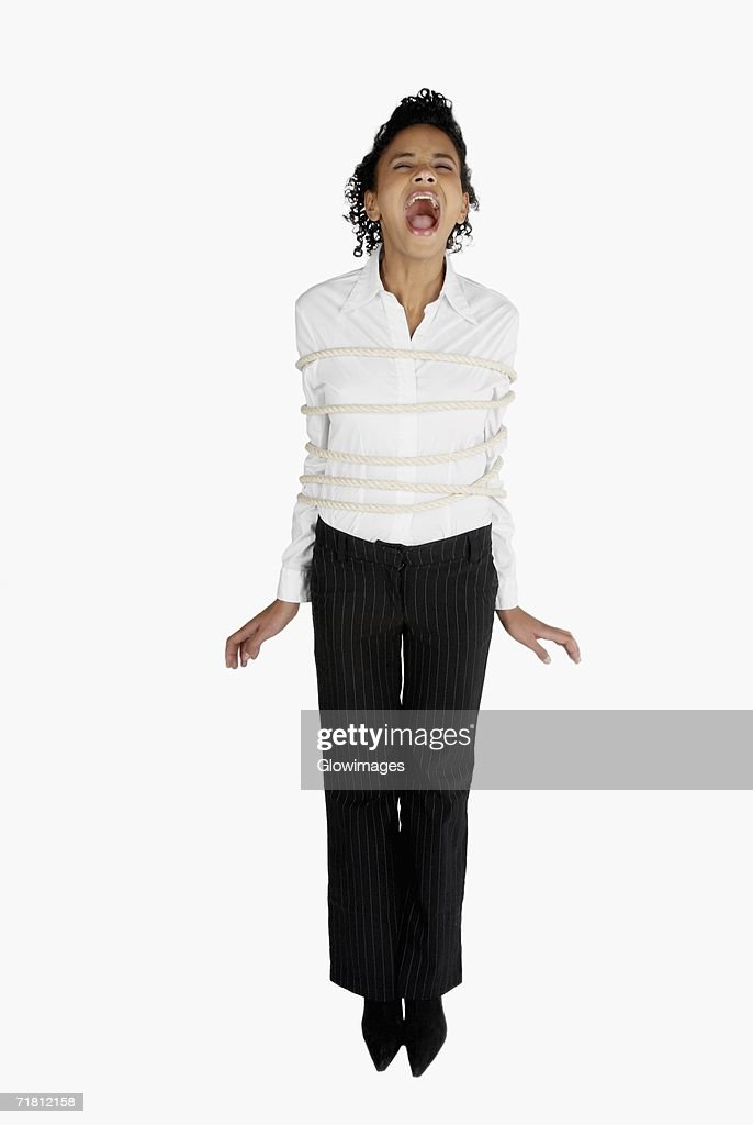 Businesswoman tied up with a rope and screaming : Stock Photo