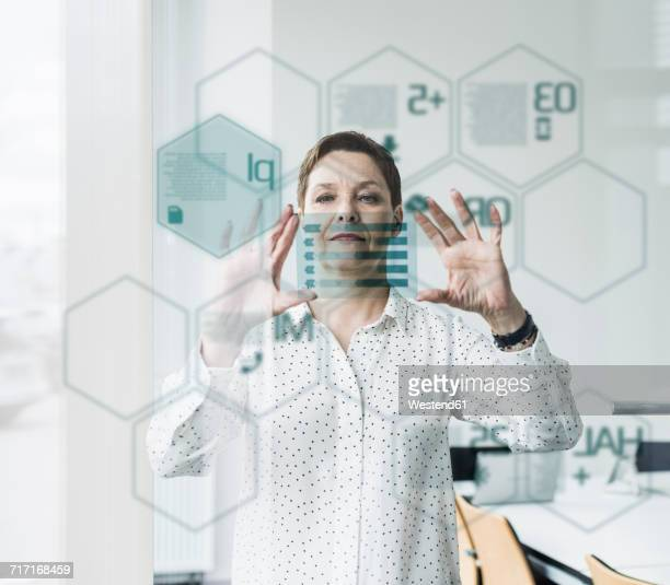 Businesswoman touching glass pane with data in office