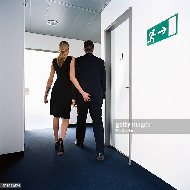 businesswoman touching man's bottom - seduction stock pictures, royalty-free photos & images
