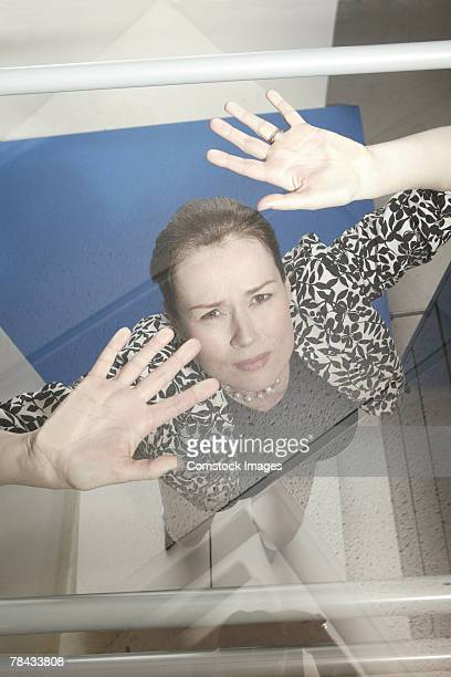 Businesswoman trapped under glass ceiling