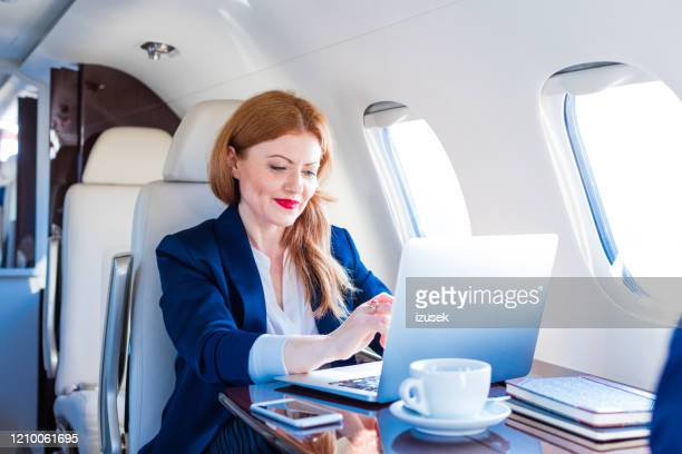 businesswoman traveling by corporate jet - high society stock pictures, royalty-free photos & images