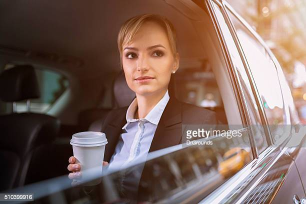 Businesswoman traveling though city in car
