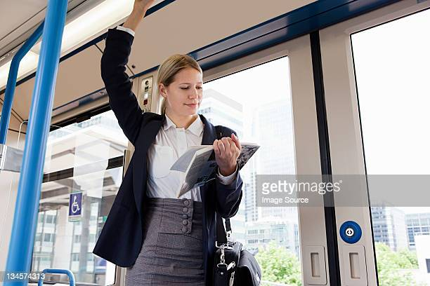 Businesswoman travelling on train with book
