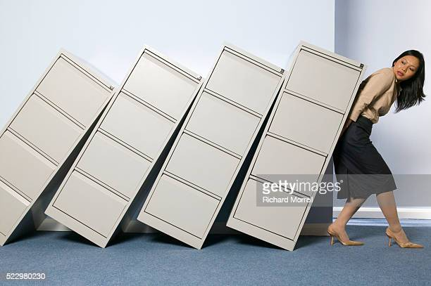 Businesswoman Trying to Hold Up File Cabinets