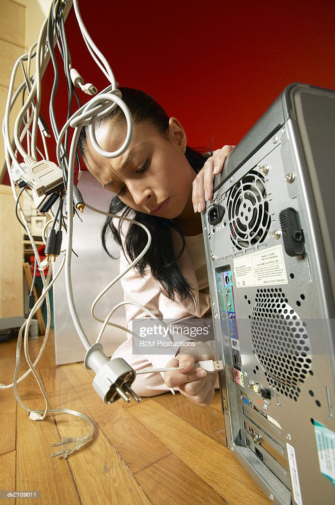 Businesswoman Trying to Plug a USB cable on the Back of a Computer : Stock Photo