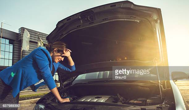 Businesswoman trying to repair her car after the breakdown.