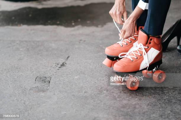 Businesswoman tying her roller skates, close up