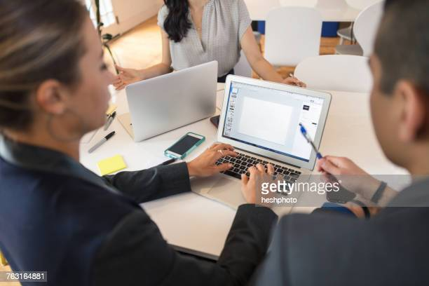 businesswoman typing on laptop at conference table meeting - heshphoto stock-fotos und bilder