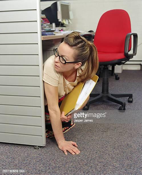 businesswoman under desk in office, holding yellow folder - 隠れる ストックフォトと画像