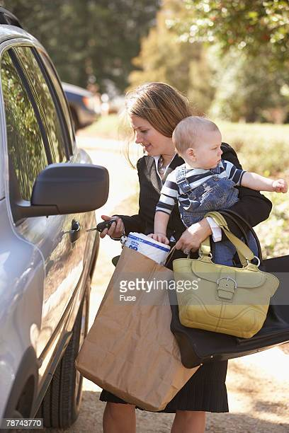 Businesswoman Unlocking Car While Holding Son