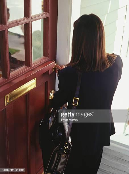 Businesswoman unlocking front door of house
