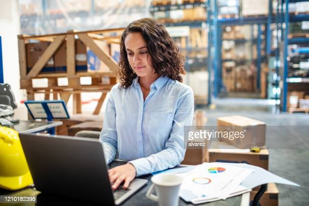businesswoman updating stocks on laptop at warehouse - distribution warehouse stock pictures, royalty-free photos & images