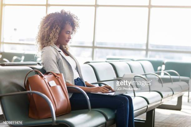 businesswoman uses laptop in airport terminal - black purse stock pictures, royalty-free photos & images