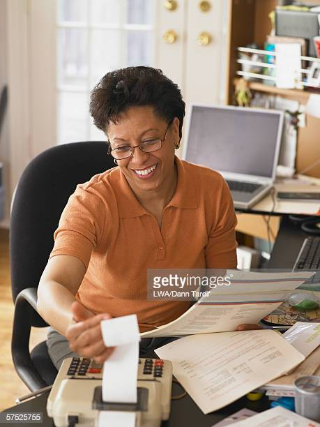 Businesswoman using a calculator at her desk