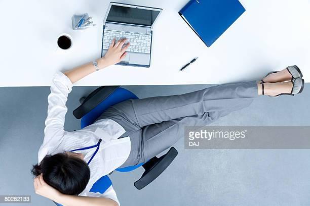 Businesswoman using a laptop, feet resting on desk, China, Beijing