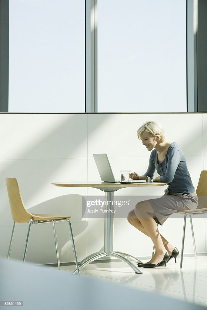 Businesswoman using a laptop, side view : Stock-Foto