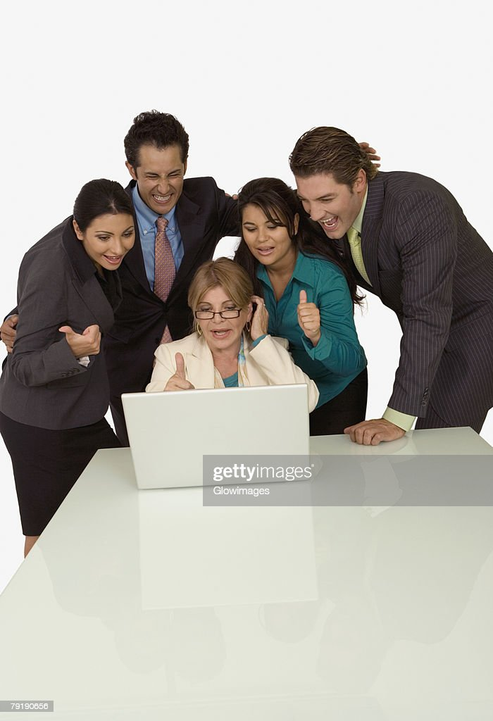 Businesswoman using a laptop with four business executives beside her : Foto de stock