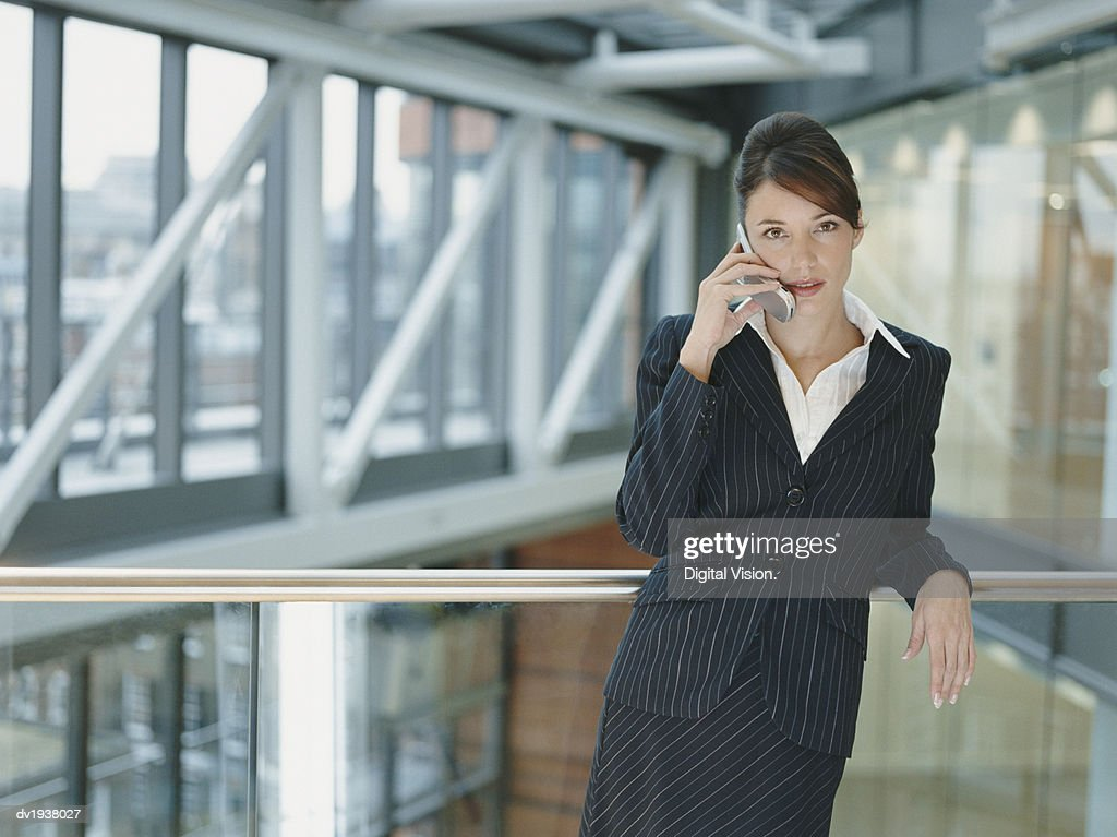 Businesswoman Using a Mobile Phone on a Balcony in an Office Building : Stock Photo