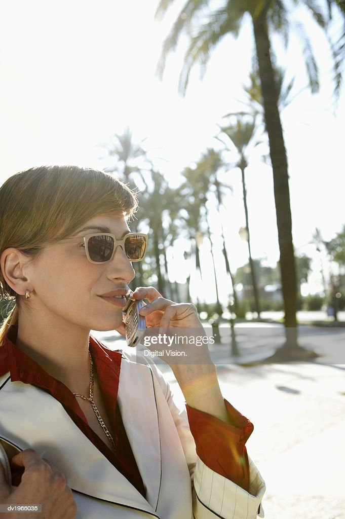 Businesswoman Using a Mobile Phone on a Street With Palm Trees : Stock Photo
