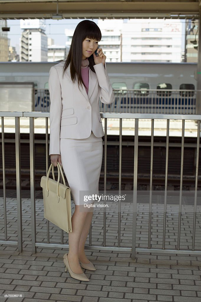 Businesswoman Using a Mobile Phone on a Train Platform : Stock Photo