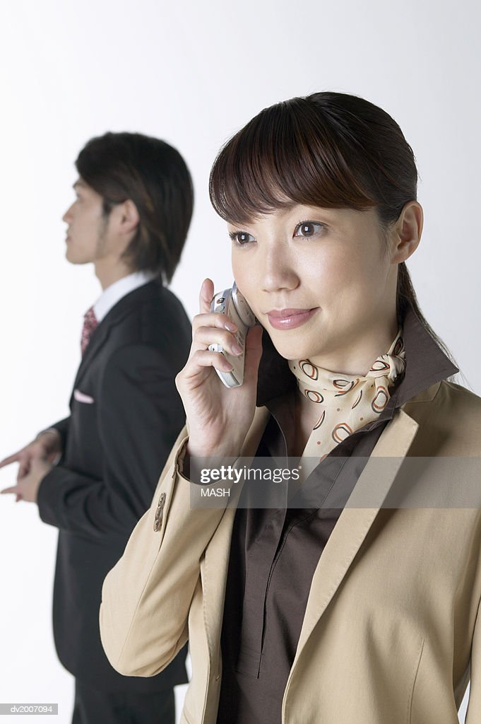 Businesswoman Using a Mobile Phone With a Businessman Standing in the Background : Stock Photo