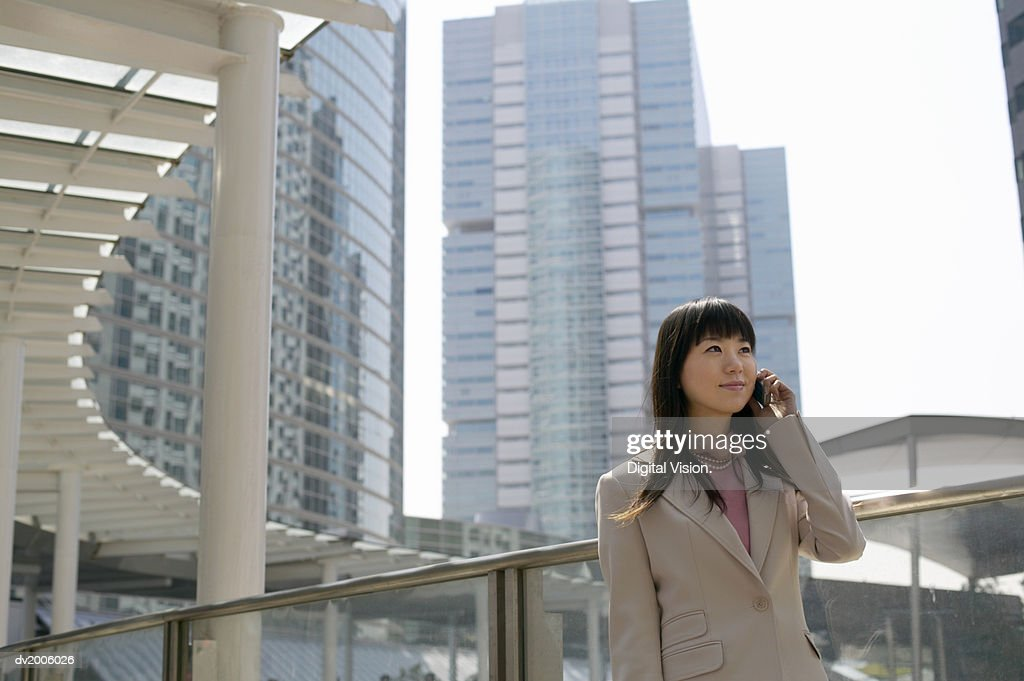 Businesswoman Using a Mobile Phone, with Office Blocks in the Background : Stock Photo