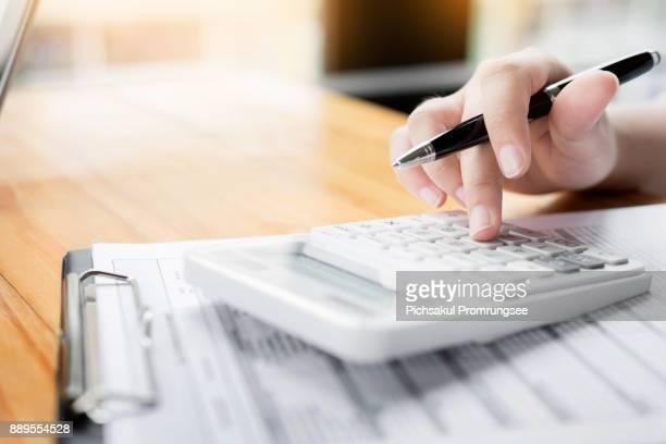 businesswoman using calculator at desk in office - rechenmaschine stock-fotos und bilder